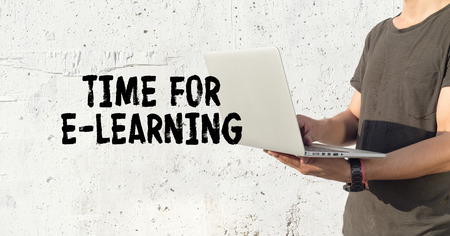 Young man using laptop and TIME FOR E-LEARNING concept on wall background Stock Photo