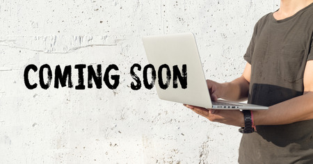 presently: Young man using laptop and COMING SOON concept on wall background
