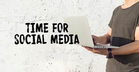 textcloud: Young man using laptop and TIME FOR SOCIAL MEDIA concept on wall background