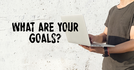 accomplishing: Young man using laptop and WHAT ARE YOUR GOALS? concept on wall background Stock Photo