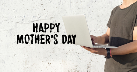 mothering: Young man using laptop and HAPPY MOTHERS DAY concept on wall background