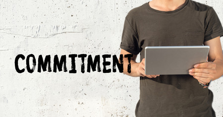 consign: Young man using tablet pc and COMMITMENT concept on wall background