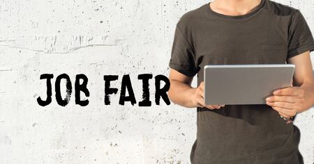 Young man using tablet pc and JOB FAIR concept on wall background