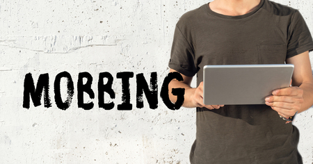mobbing: Young man using tablet pc and MOBBING concept on wall background