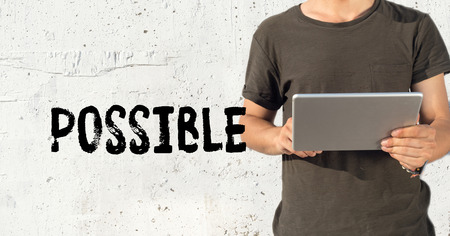 unachievable: Young man using tablet pc and POSSIBLE concept on wall background