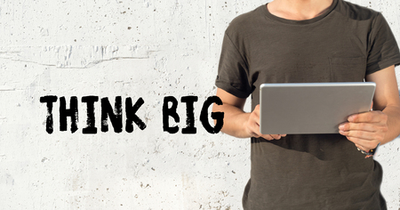 surpassing: Young man using tablet pc and THINK BIG concept on wall background Stock Photo