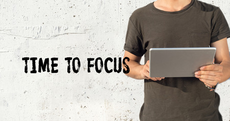 distinctness: Young man using tablet pc and TIME TO FOCUS concept on wall background