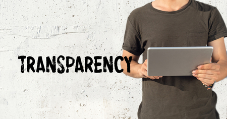 evident: Young man using tablet pc and TRANSPARENCY concept on wall background Stock Photo