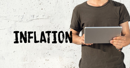 price uncertainty: Young man using tablet pc and INFLATION concept on wall background