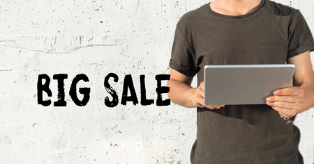 gift spending: Young man using tablet pc and BIG SALE concept on wall background Stock Photo