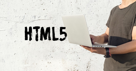 html5: Young man using laptop and HTML5 concept on wall background