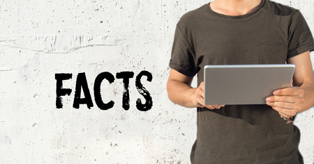 uprightness: Young man using tablet pc and FACTS concept on wall background