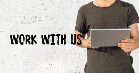 new recruit: Young man using tablet pc and WORK WITH US concept on wall background