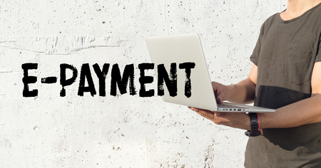 e systems: Young man using laptop and E-PAYMENT concept on wall background Stock Photo