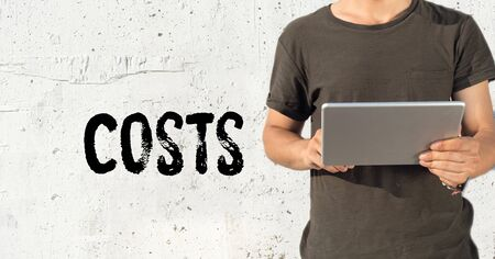 reorganization: Young man using tablet pc and COSTS concept on wall background Stock Photo