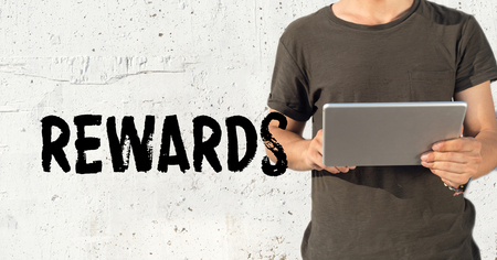 perks: Young man using tablet pc and REWARDS concept on wall background
