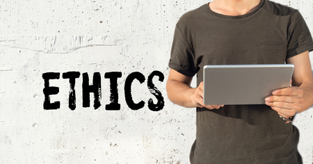 work ethic responsibilities: Young man using tablet pc and ETHICS concept on wall background Stock Photo