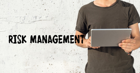 adult  body writing: Young man using tablet pc and RISK MANAGEMENT concept on wall background