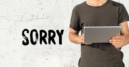 remorse: Young man using tablet pc and SORRY concept on wall background