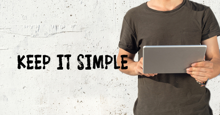 cogent: Young man using tablet pc and KEEP IT SIMPLE concept on wall background