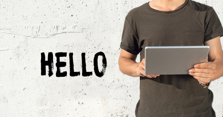english ethnicity: Young man using tablet pc and HELLO concept on wall background