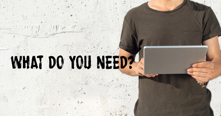 adult  body writing: Young man using tablet pc and WHAT DO YOU NEED? concept on wall background Stock Photo