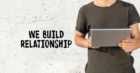 social grace: Young man using tablet pc and WE BUILD RELATIONSHIP concept on wall background