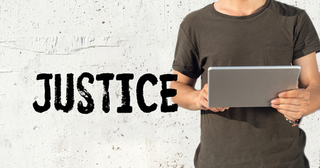justness: Young man using tablet pc and JUSTICE concept on wall background Stock Photo