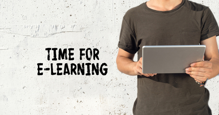 Young man using tablet pc and TIME FOR E-LEARNING concept on wall background