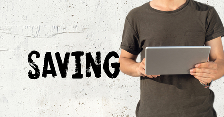 frugality: Young man using tablet pc and SAVING concept on wall background
