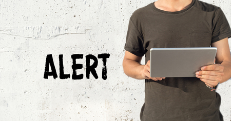 spy ware: Young man using tablet pc and ALERT concept on wall background