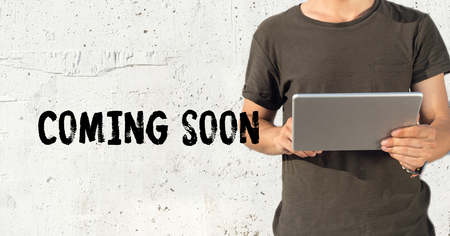 presently: Young man using tablet pc and COMING SOON concept on wall background