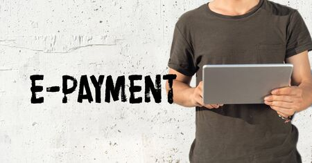 epayment: Young man using tablet pc and E-PAYMENT concept on wall background