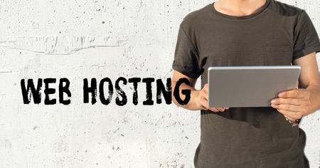 Young man using tablet pc and WEB HOSTING concept on wall background