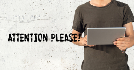 peril: Young man using tablet pc and ATTENTION PLEASE! concept on wall background Stock Photo