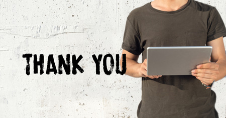 acknowledgment: Young man using tablet pc and THANK YOU concept on wall background Stock Photo