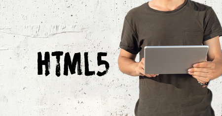 html5: Young man using tablet pc and HTML5 concept on wall background