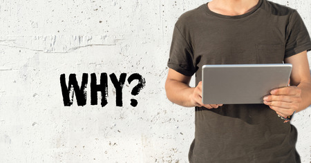 querying: Young man using tablet pc and WHY? concept on wall background Stock Photo
