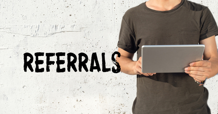 referrals: Young man using tablet pc and REFERRALS concept on wall background