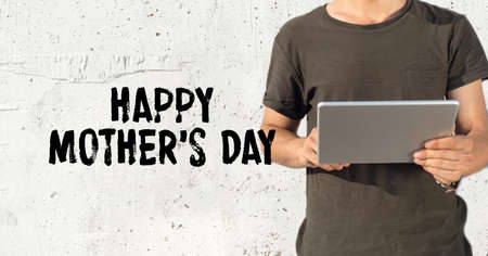mothering: Young man using tablet pc and HAPPY MOTHERS DAY concept on wall background