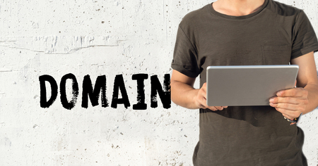 edu: Young man using tablet pc and DOMAIN concept on wall background