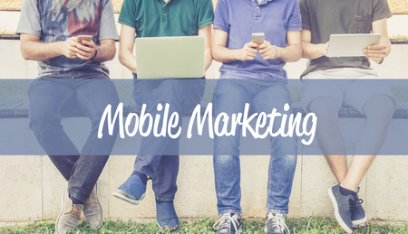 mobile marketing: Group of people using mobile devices and MOBILE MARKETING concept Stock Photo