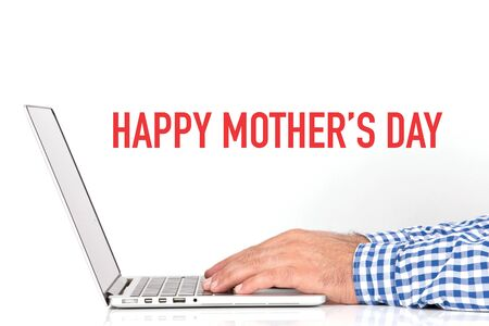 mothering: Young man working on desk and HAPPY MOTHERS DAY concept on white background