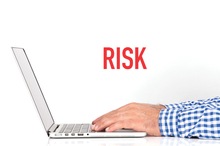 risky situation: Young man working on desk and RISK concept on white background