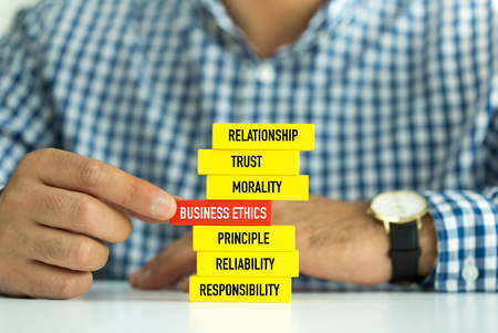 principled: Businessman Building BUSINESS ETHICS Concept with Wooden Blocks
