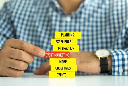 Businessman Building EVENT MARKETING concept with Wooden Blocks Stock Photo