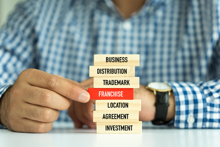 franchising: Businessman Building FRANCHISE concept with Wooden Blocks Stock Photo
