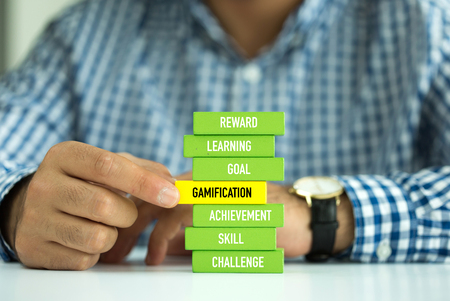 Businessman Building GAMIFICATION concept with Wooden Blocks