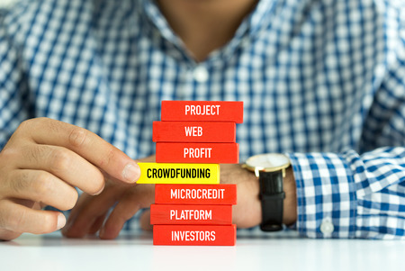 Businessman Building CROWDFUNDING Concept with Wooden Blocks