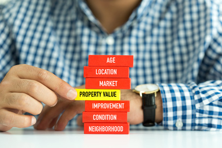 Businessman Building PROPERTY VALUE concept with Wooden Blocks